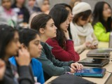 Several young women listen to a presentation during the Technovation Challenge.