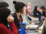 A young woman listens to a presentation during the Technovation Challenge.