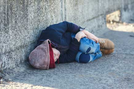 Spening on social programs in Ottawa lags behind: a homeless person lies on the street in winter clothing.