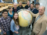 Ernst and his group gather around a globe.