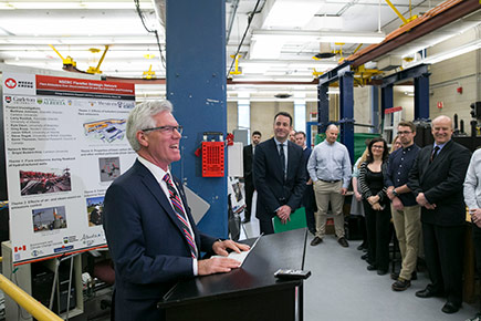 Minister Jim Carr speaks at a podium during a visit to Carleton to promote clean technology.