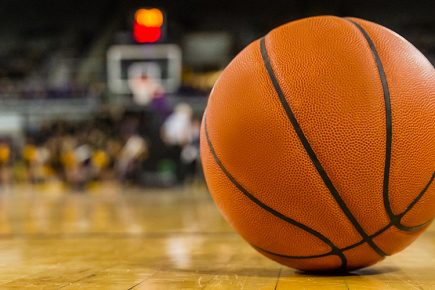 A closeup of a basketball sitting on the court in a large stadium filled with fans.