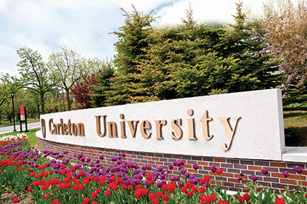 The Carleton University sign, ensconsed with tulips, at Bronson Avenue on a sunny day