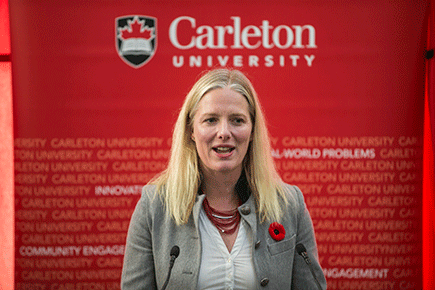 Catherine McKenna announces SIF funding at a podium at Carleton.