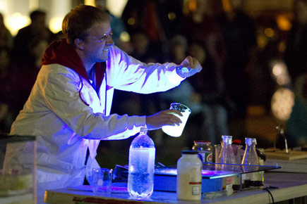 A professor adds chemicals to a bubbling beaker during the Chemistry Magic Show.