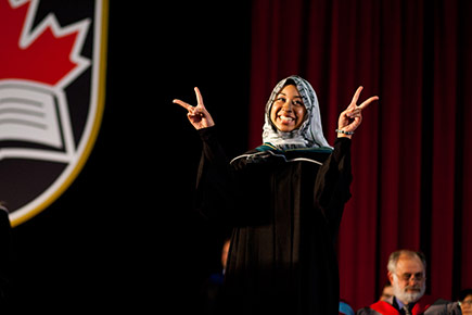 A Carleton student gives the peace sign before receiving her degree on stage.