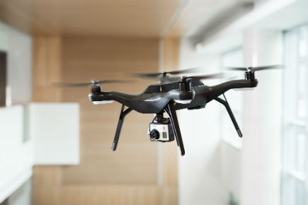 A quadcopter drone flies indoors at Carleton's Canal Building.