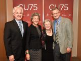 Erica Cherney poses for a picture with members of her family in front of a CU75 backdrop