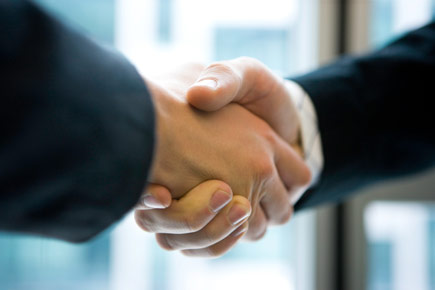 A closeup of two hands during a handshake.