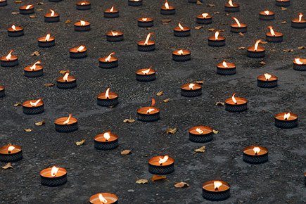 Lights of remembrance are laid out on the ground during a Holocaust Vigil
