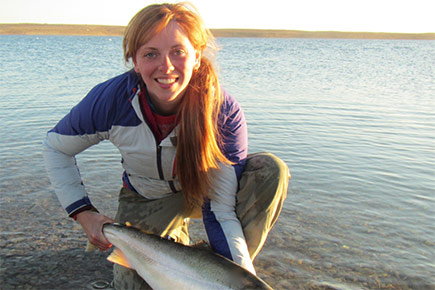 Jacqueline Chapman, one of the winner of the 2016 GRIT Awards, holds a fish on a river shore.