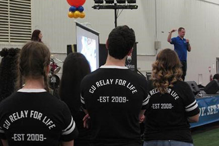 Relay for Life participants listen to a speaker in the Fieldhouse