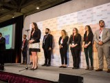 A team member from the Sprott School of Business describes their project on stage.
