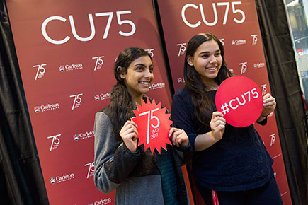 Two students pose against a CU75 backdrop.