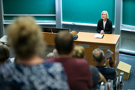 President Runte delivers the State of the University address in September 2016 in front of a chalkboard as a crowd of onlookers listens.