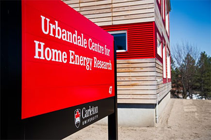 A large sign sits in front of the Urbandale Centre for Home Energy Research on a sunny day.