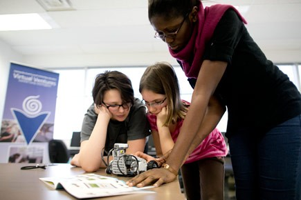 Two girls and an instructor work on a robot during a Virtual Ventures program.