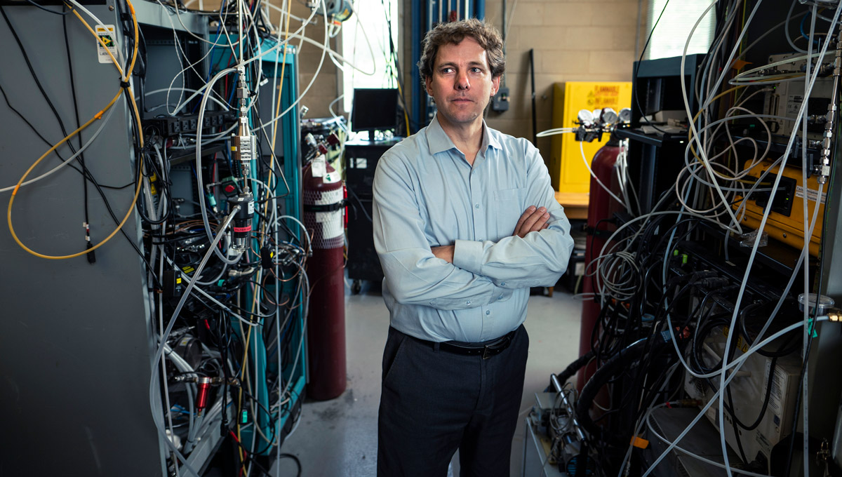 Matthew Johnson poses in their lab surrounded by electronic gear and monitoring equipment.