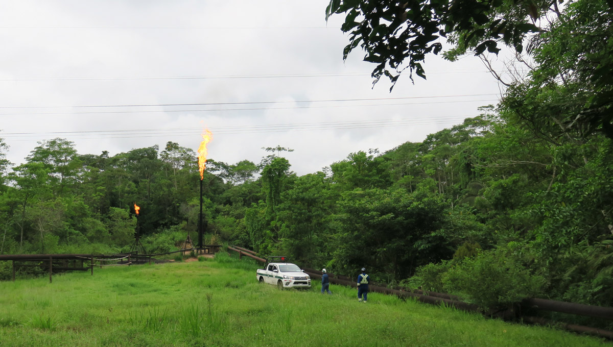 The FlareNet team stands near a truck and a gas flare in the Amazon.