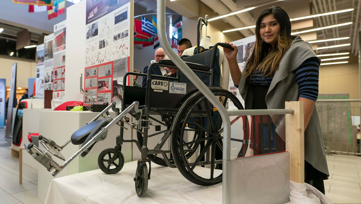 Amira Ashraf stands with a wheelchair.