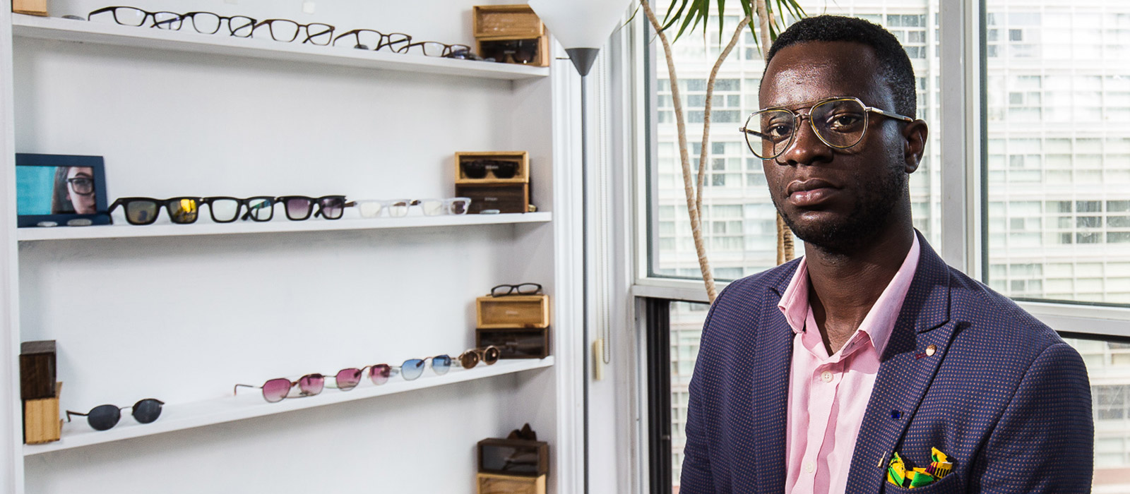 Nana Osei in his downtown Toronto workshop with eyeglasses on a wall in the background.