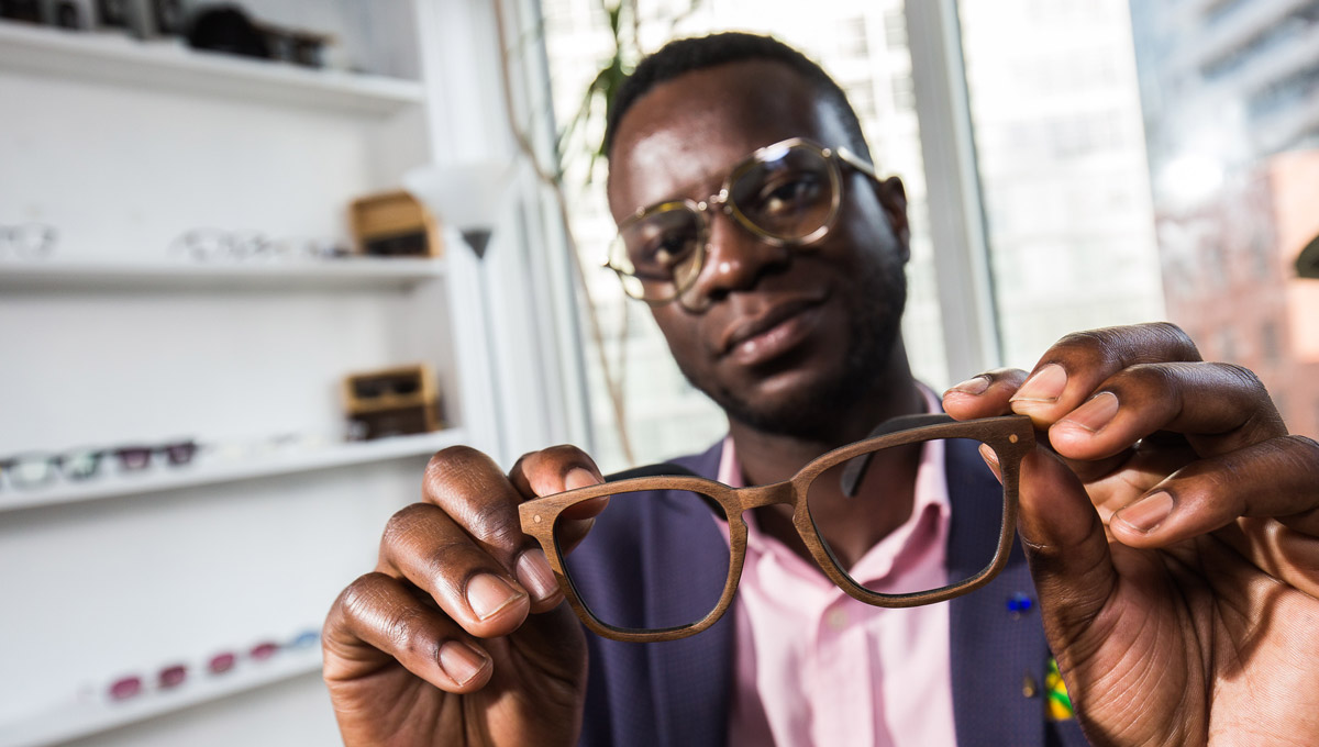 Nana Osei holds a pair of his sustainable glasses.