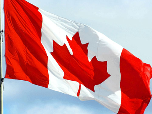 A Canadian flag waves in the wind.