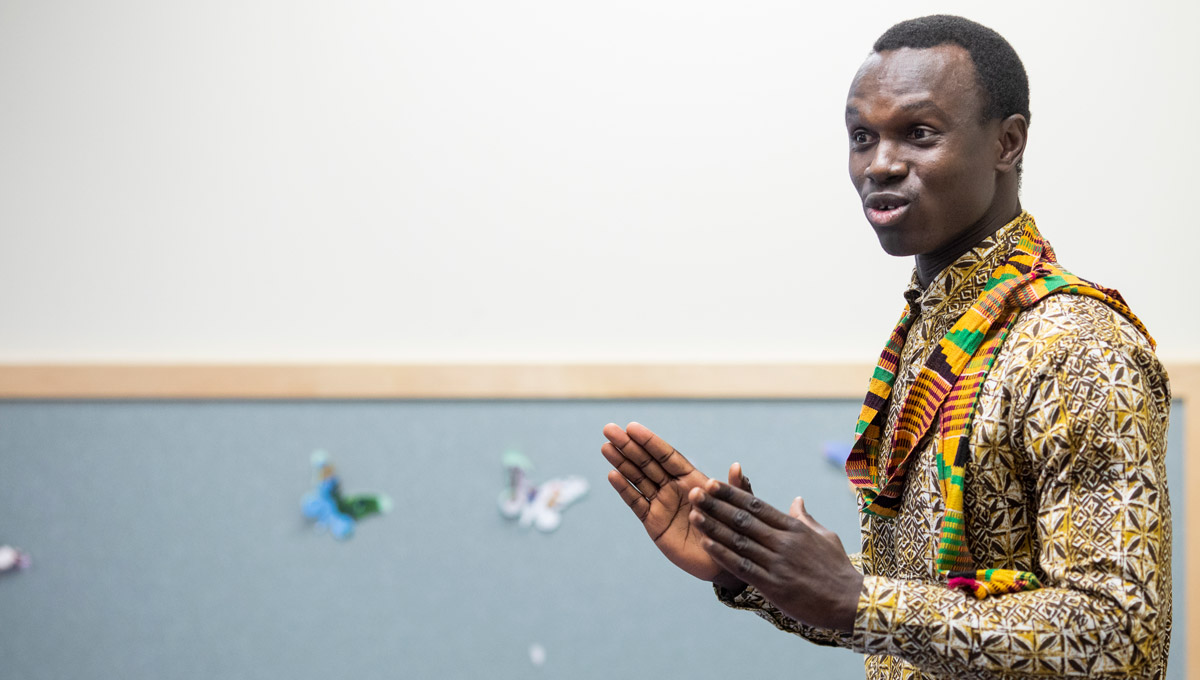 A man in a colourful shirt and a tradition scarf presents during the Climate Change Conversations.