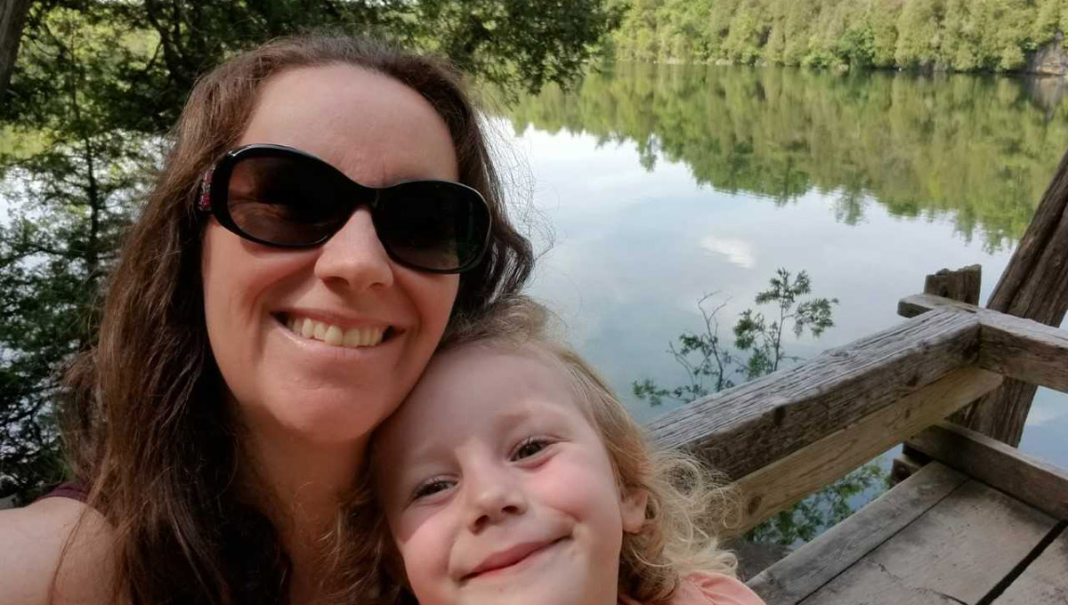 Dr. Catherine Cullingham smiles while hugging her small daughter beside a forested-lake.