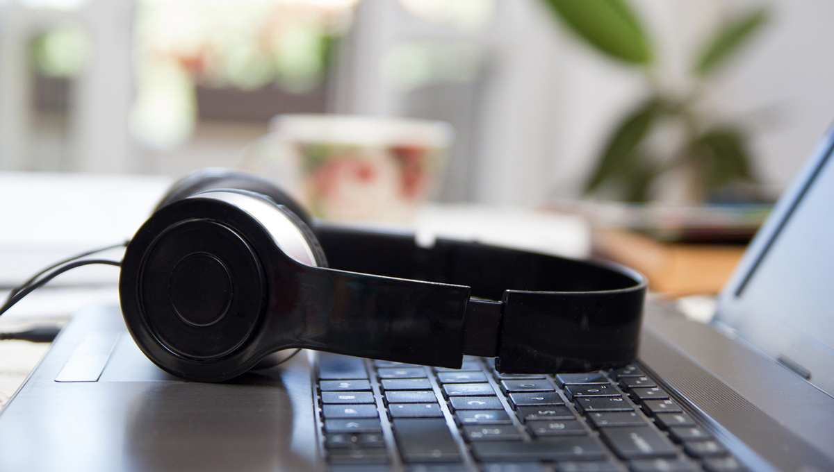 A pair of headphones lays on the keyboard of a laptop