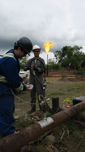 Members of the FlareNet team work on an oil and gas line, and a gas flare emitting flame in the background.