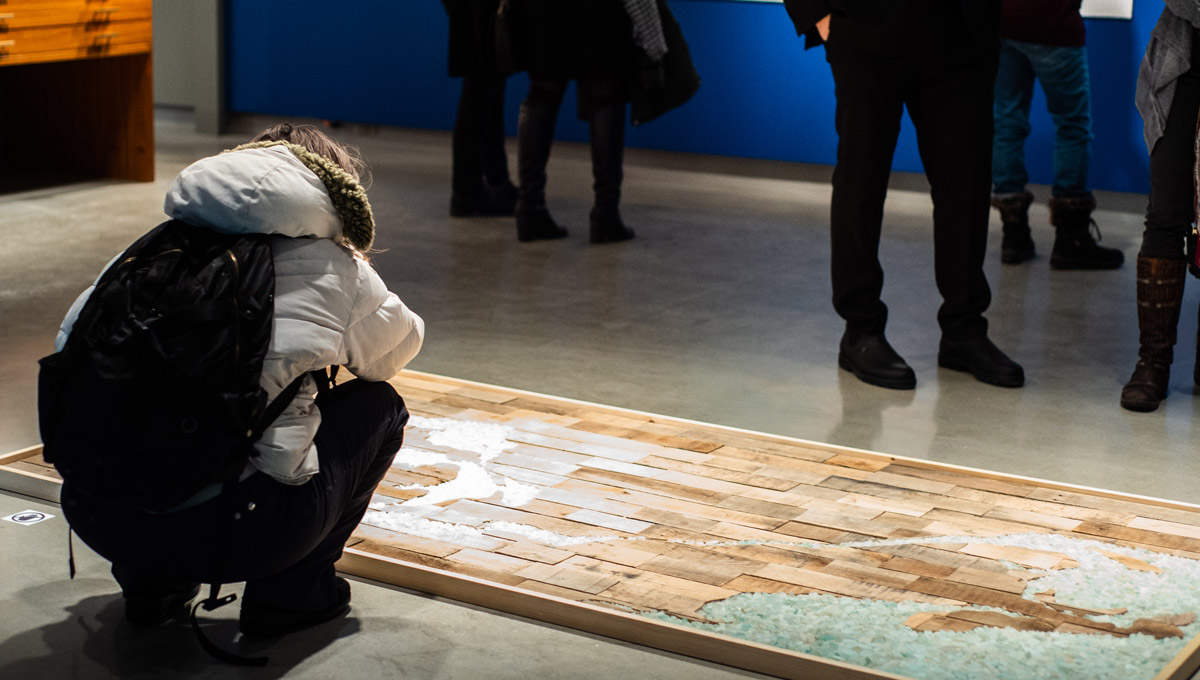 An exhibit attendee peers at Jesse Stewart's Time and Tide, a wood and beach glass installation on the floor of the Ottawa Art Gallery.