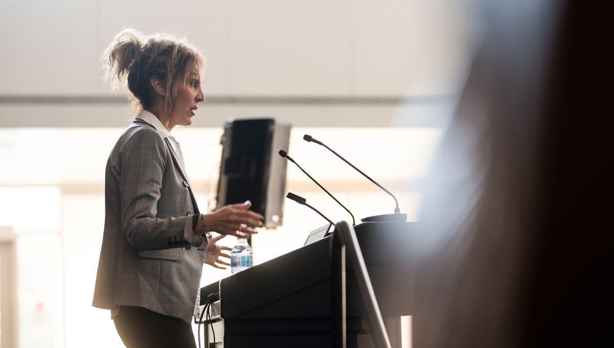 Prof. Joanna Pozzulo speaks at a podium during Psychology Mental Health Day.