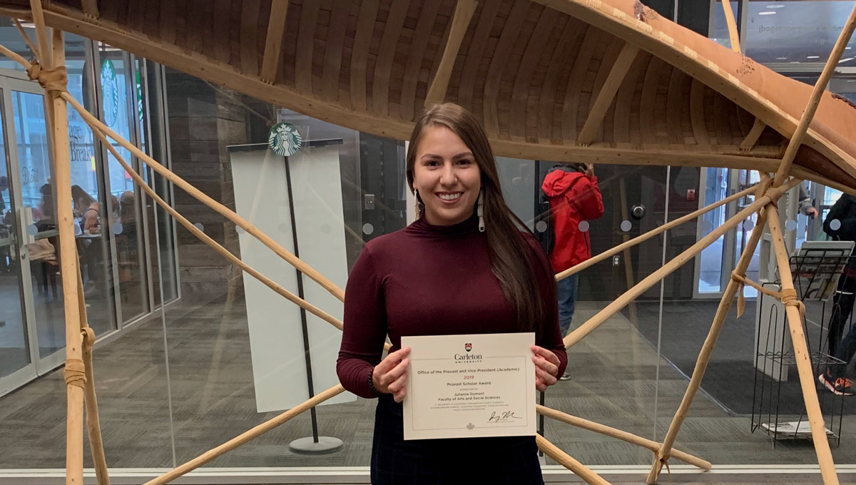 Julianne Dumont holds her Provost's Scholar award while standing in front of a birchbark canoe in MacOdrum Library.
