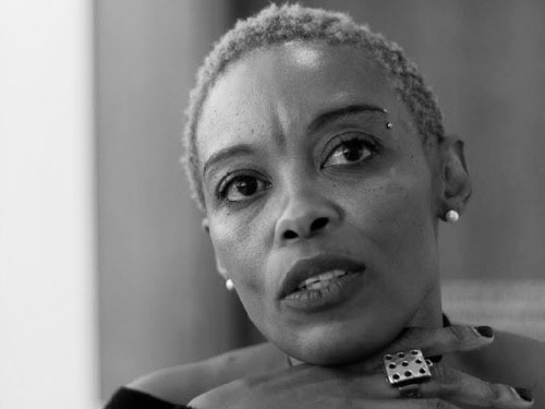 A photograph of author Kagiso Molope, her chin rests on top of her hands.