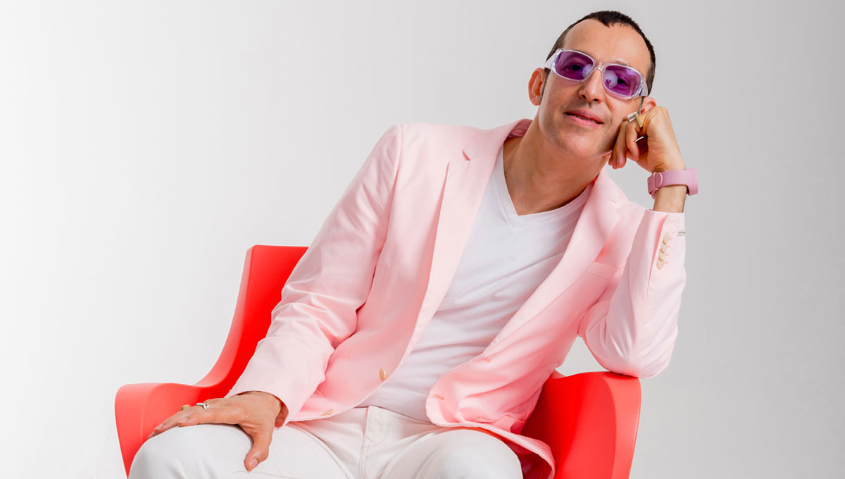 Karim Rashid sits in a red chair of his own design.