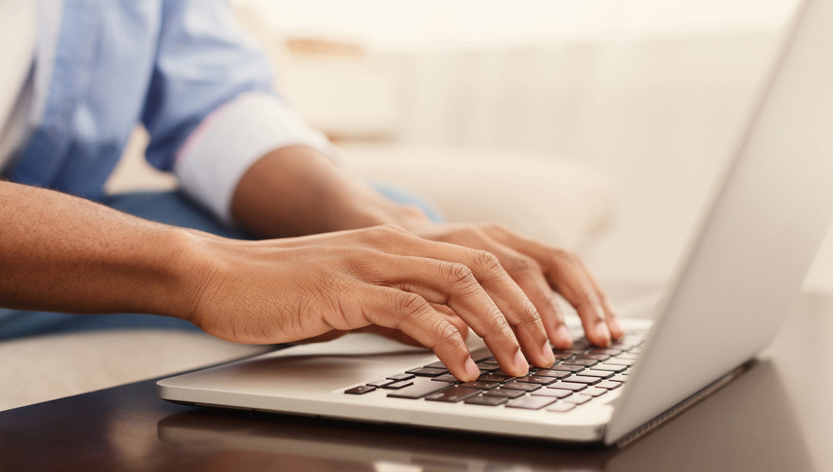 A close up image of a person's hands typing on a computer at home.