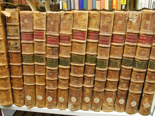 Old books lined up with their spines facing the viewer on a library shelf.