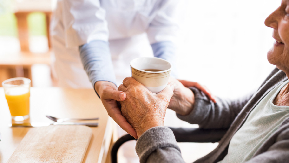 A retirement home worker helps an elderly resident.