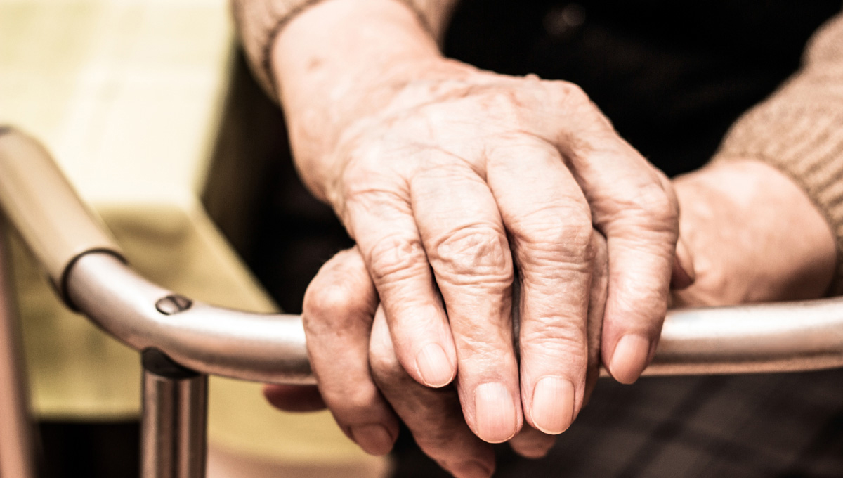 A photo of an elderly person's hands holding on to a walker.