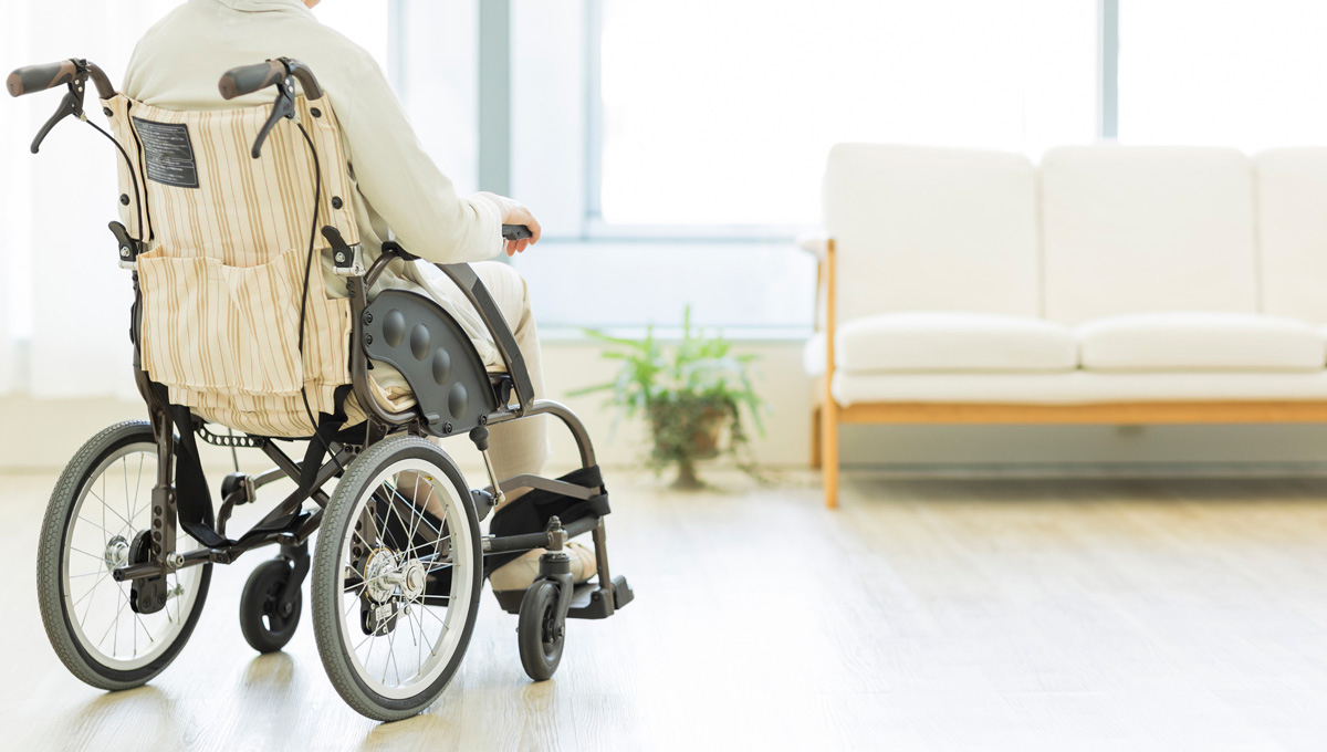 A woman sits in a wheelchair in a retirement home lounge. A houseplant and couch are in the background.