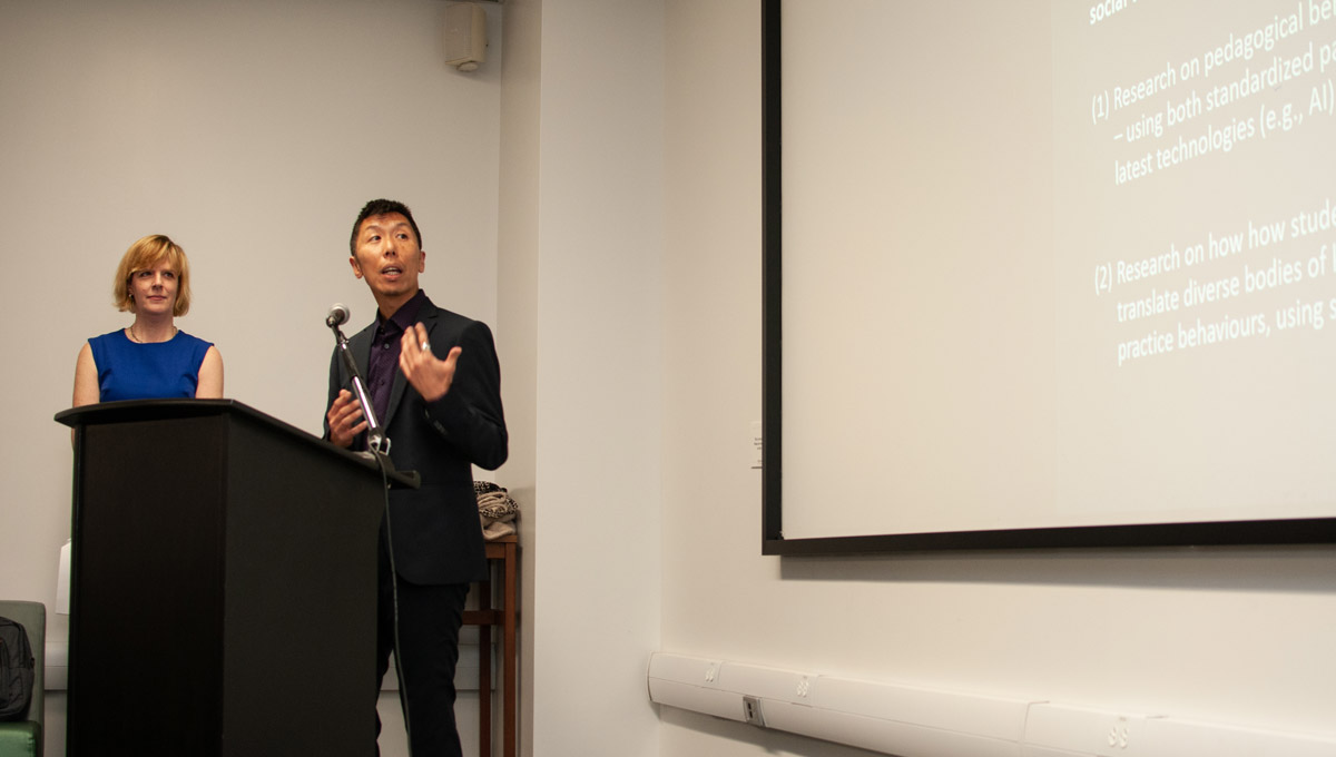 Kenta Asakura speaks at a microphone while Prof. Sarah Todd looks on.