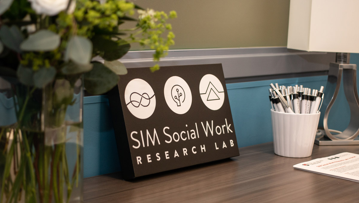 A SIM Lab sign sits on a desk next to a cup full of pens