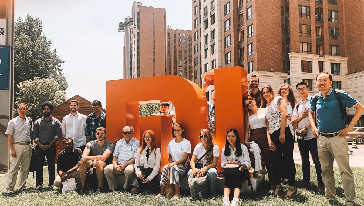 The Carleton delegation gathers around a large, three dimensional version of the Xiaomi logo in an outdoor setting.