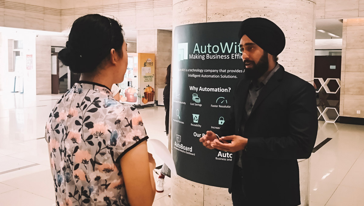 Jyot Singh pitces his company, AutoWit, to a potential investor. An AutoWit poster is hung on a pillar behind him as he speaks.