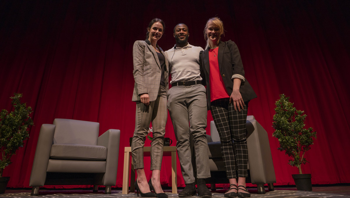 Tessa Virtue poses with two students onstage at the SOAR Student Leadership Conference.