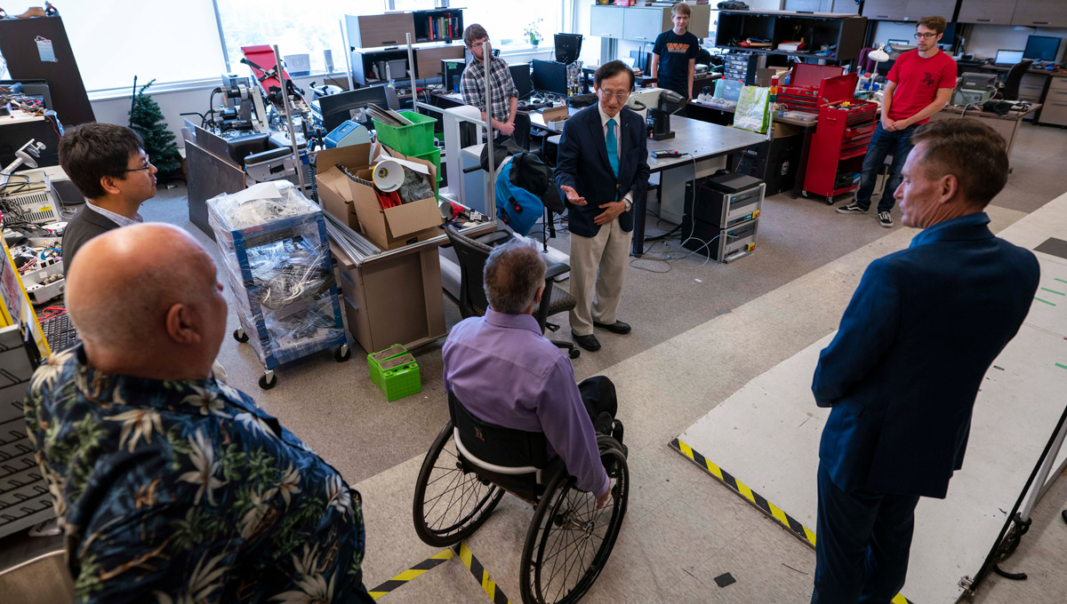 Minister Raymond Cho tours an engineering lab filled with accessibility devices.