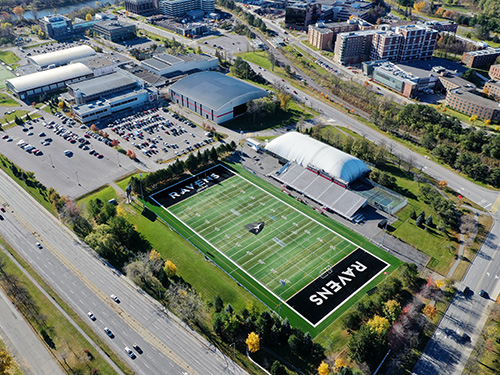 An aerial shot of the Carleton University campus. The football field can be seen with the word Ravens in the end zone.
