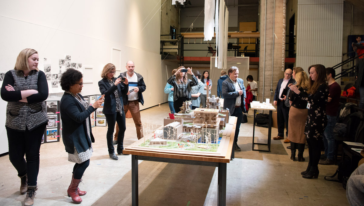 Industry invitees hear the students' design ideas and look over their model of the Booth Street complex.