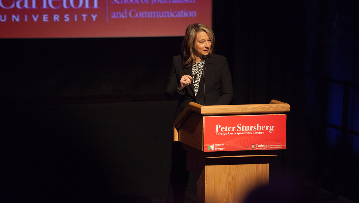 Adrienne Arsenault speaks at a podium emblazoned with the words Peter Stursberg Foreign Correspondents Lecture